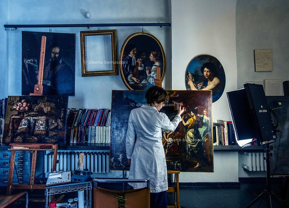 Rome, the coservative studio Merlini Storti, Barbara Rossodivita removing superficial dust on an 18th-century oil on canvas inside the studio