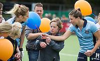 LAREN - G hockey (voor spelers met een verstandelijke beperking) spelers lopen op met de speelsters, met Kim Lammers en Willemijn Bos (l)   bij de presentatie van de teams bij de wedstrijd tussen de dames van Laren en SCHC. COPYRIGHT KOEN SUYK