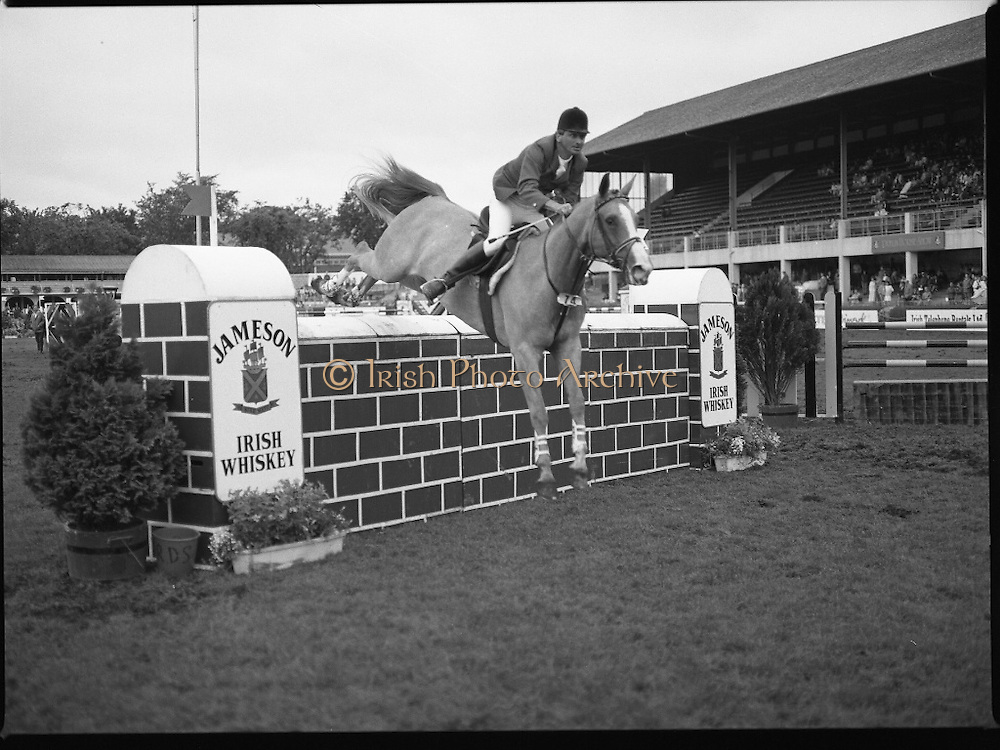 Jameson Whiskey International at the Dublin Horse Show.  (R39).1986..07.08.1986..08.07.1986..7th August 1986..The Jameson Whiskey International at the Dublin Horse Show in the RDS was won by Peter Charles of Great Britain. He rode 'Merrimandias' to victory in the event...Image shows Klaus Reinacher (France) in the Jameson Whiskey International clearing the wall aboard his mount 'Desiree' at the Horse Show. Jameson's, Irish, Whiskey, jameson,
