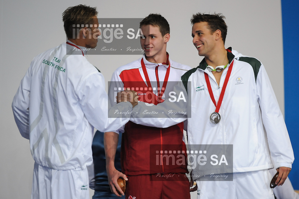 GLASGOW, SCOTLAND - JULY 25: Roland Schoeman and Chad le Clos congratulate each other as Benjamin Proud of England (gold) looks on during the medal ceremony of the mens 50m butterfly on day 2 of the 20th Commonwealth Games at Tollcross Swimming Centre on July 25, 2014 in Glasgow, Scotland. (Photo by Roger Sedres/ImageSA)