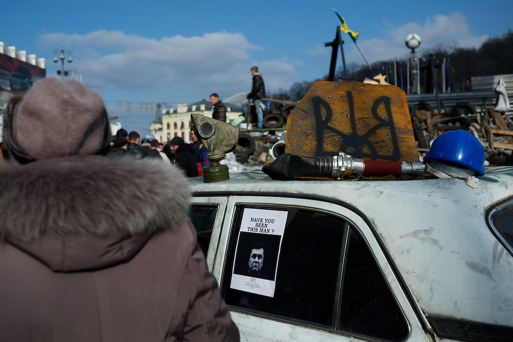 KIEV, UKRAINE - February 24, 2014: People pass by a poster with a picture of the deposed president Viktor Yanukovych, a wanted man on the run in Ukraine. CREDIT: Paulo Nunes dos Santos