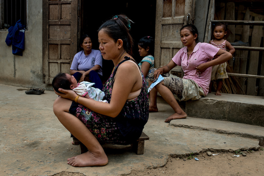 A woman with her newborn baby in the village of Khoc Kham. The village is not connected to the main electrical grid and many residents operate their own turbines to power lights and sometimes small appliances.
