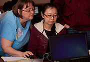Accounting Instructor Susanne Freeland (Left) helps international student Xiuming Jin complete her tax forms at a volunteer income tax assistance program offered by the College of Business at Ohio University.