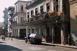 Street scene in Havana; Cuba; showing water lorry parked outside apartments,