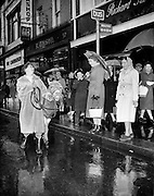 """""""Bus Fares Up"""" .1960..15.01.1960..01 15 1960..15 January 1960...With an imminent rise in bus fares on the cards Maureen Potter,Ireland's best known entertainer, expressed her outrage by getting her own mode of transport, a donkey...Image shows Maureen, and donkey, discussing the fare hike with amused commuters at a bus stop in Grafton Street, Dublin."""