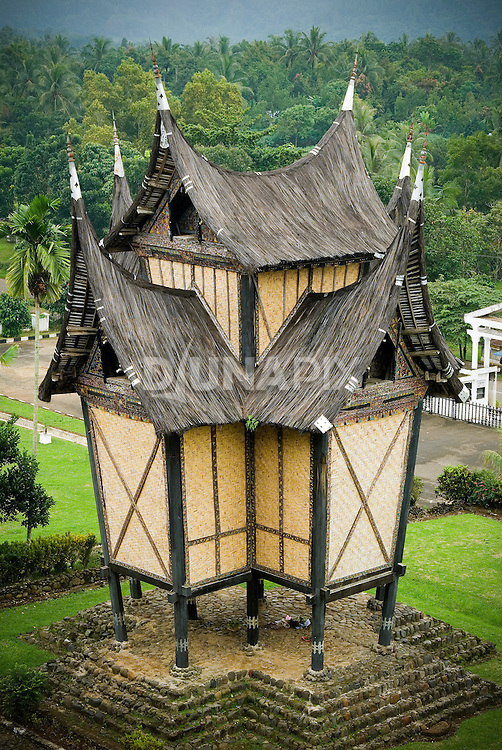 """A traditional """"gonjong"""" rice barn decorates the grounds of the Pagaruyung Palace, Batusangkar, West Sumatra. The spired, buffalo horn roof is typical of Minangkabau architecture."""