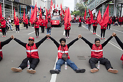 May 1, 2019 - Jakarta, Indonesia - Workers seen seating across the road with joined hands during the commemoration..Workers marched demonstrating while commemorating May Day 2019, they demand for the government to immediately revoke Government Regulation No. 78 of 2015 concerning Wages. (Credit Image: © Nick Hanoatubun/SOPA Images via ZUMA Wire)