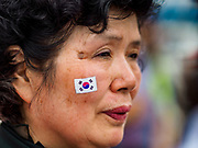09 JUNE 2018 - SEOUL, SOUTH KOREA: A woman with a South Korean flag sticker on her cheek marches in a pro-American rally in downtown Seoul. Participants said they wanted to thank the US for supporting South Korea and they hope the US will continue to support South Korea. Many were also opposed to ongoing negotiations with North Korea because they don't think Kim Jong-un can be trusted to denuclearize or to not attack South Korea.     PHOTO BY JACK KURTZ