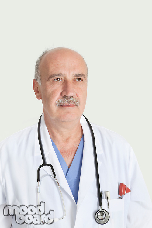 Senior male doctor with stethoscope over gray background
