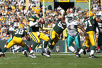 GREEN BAY, WI - OCTOBER 17: Aaron Rodgers #12 of the Green Bay Packers is pressured by Randy Starks #94 of the Miami Dolphins at Lambeau Field on October 17, 2010 in Green Bay, Wisconsin. The Dolphins defeated the Packers 23-20 in overtime. (Photo by Tom Hauck) Player:Aaron Rodgers;Randy Starks