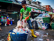 "04 DECEMBER 2018 - BANGKOK, THAILAND:  A Burmese worker cleans up plastic waste in Khlong Toei market. The issue of plastic waste became a public one in early June when a whale in Thai waters died after ingesting 18 pounds of plastic. In a recent report, Ocean Conservancy claimed that Thailand, China, Indonesia, the Philippines, and Vietnam were responsible for as much as 60 percent of the plastic waste in the world's oceans. Khlong Toey (also called Khlong Toei) Market is one of the largest ""wet markets"" in Thailand. December 4 was supposed to be a plastic free day in Bangkok but many market venders continued to use plastic.    PHOTO BY JACK KURTZ"