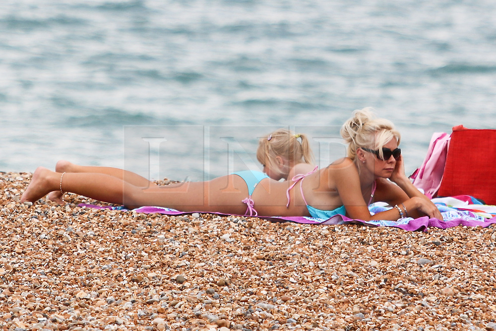 © Licensed to London News Pictures. 01/07/2015. Brighton, UK. People Sunbathe on Brighton beach and swim in the sea on the hottest day of the year, today July 1st 2015. Photo credit : Hugo Michiels/LNP01/07/2015. Brighton, UK. People Sunbathe on Brighton beach and swim in the sea on the hottest day of the year, today July 1st 2015. Photo credit : Hugo Michiels/LNP