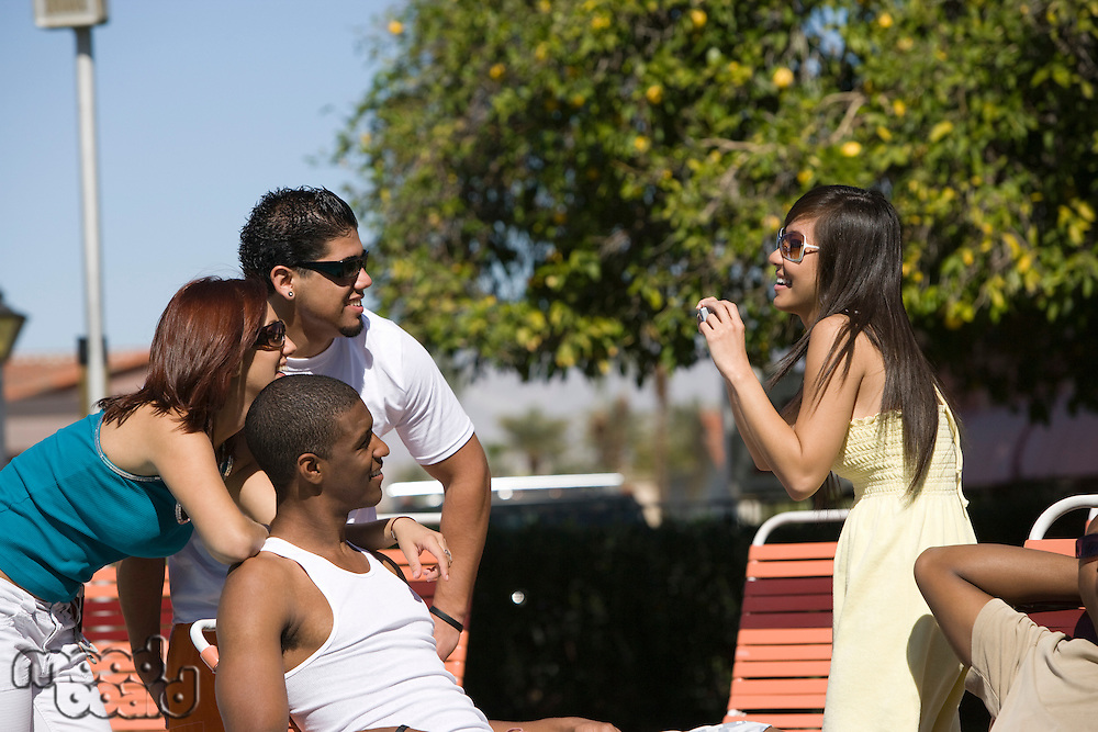 Young Woman Photographing Friends Outdoor