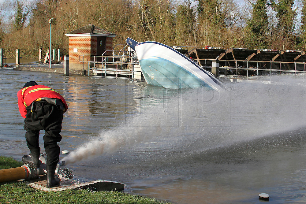 © Licensed to London News Pictures. 17/02/2014. Egham, UK.  Water is pumped back into to the Thames near to an upturned boat against Bell Wier Fire And Rescue Services Set up pumps to clear the A308 Windsor Road near Runnymede. Photo credit : John Maxwell-Roberts/LNP