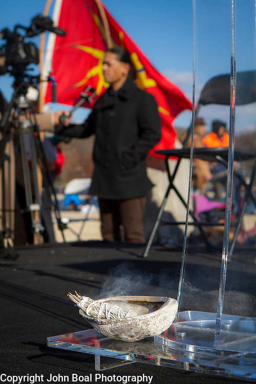 Sage burns beneath the podium on a stage prior to a protest and march from in front of the U.S. Capitol to the EPA, about the North Dakota Access Pipeline, as well as the effort to free Leonard Peltier.  Saturday, December 10, 2016. John Boal Photography