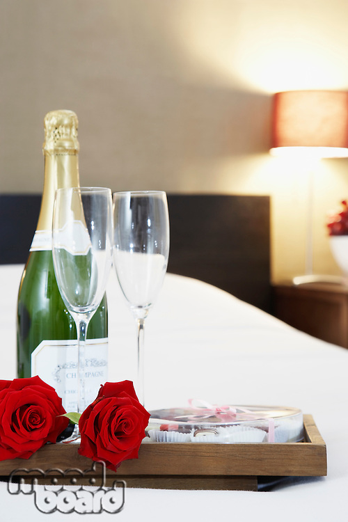 Champagne and flutes on bed