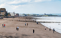 Portobello, Scotland, UK. 9 May 2020. Images from holiday weekend Saturday afternoon during Covid-19 lockdown on promenade at Portobello. Promenade and beach were relatively quiet with a low key police presence. Pictured; View along beach showing social distancing of people. Iain Masterton/Alamy Live News