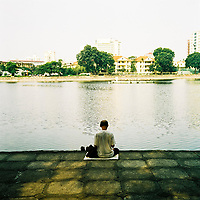 A man sits by a small lake in Hanoi, Vietnam.