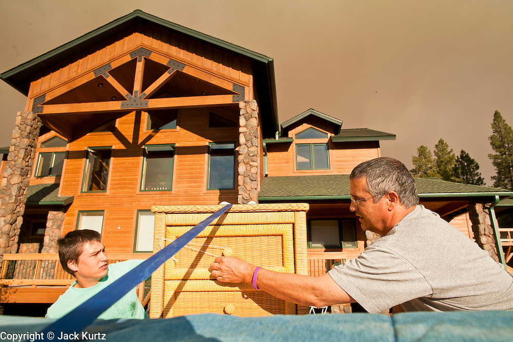 "04 JUNE 2011 - GREER, AZ: Jim Tress (CQ) and his son Thomas Tress (CQ) pack up their home in Greer before going back to Tucson.  The fire grew to more than 140,000 acres early Saturday with zero containment. A ""Type I"" incident command team has taken command of the fire.  PHOTO BY JACK KURTZ"