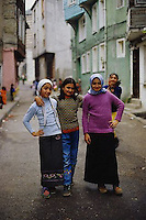 2001, Istanbul, Turkey --- Three teenage girls pose together on a residential street. Two wear traditional Muslim scarves and ankle-length skirts, the third wears blue jeans. --- Image by © Owen Franken/CORBIS