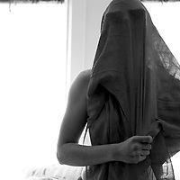 A young woman with material covering her head