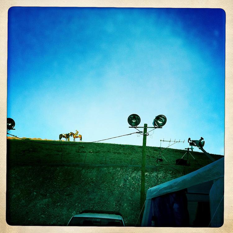 """Una pareja de policias montados resguardan las cercanias de la Mina San Jose. Plan B, es un ensayo fotografico basado en aquellas cosas que la mirada somera no permite ver, de los días de espera, angustia, soledad y fe que las familias de los 33 hombres atrapados en la mina San Jose dejaron en el paisaje arido del desierto de Atacama tras el esperado rescate. """"Plan B"""", tambien es un acto de fe personal, por intentar plasmar en un relato diferente, sin más pretensión que la mirada interna a los sentimientos que esa montaña atrapó implacable y para siempre, pero que bajo la mirada superficial de los medios no permite escudriñar por tratarse de pequeños fragmentos que apelan a emociones individuales y no a la masividad que persiguen los reportes de prensa. Este ensayo es una invitación abierta a descubrir los pequeños milagros que florecieron en la montaña y en el día a día de cada una de las familias que nunca dejaron de creer en la vida, aun así se enfrentaran a la inmensidad del desierto y a las minimas espectativas de vida que el lugar entregaba.""""Plan B"""", esta constituido por fotografías ejecutadas en su totalidad con un telefono iPhone 4 y la aplicacion Hipstamatic. ROBERTO CANDIA / REVISTA NUESTRA MIRADA"""