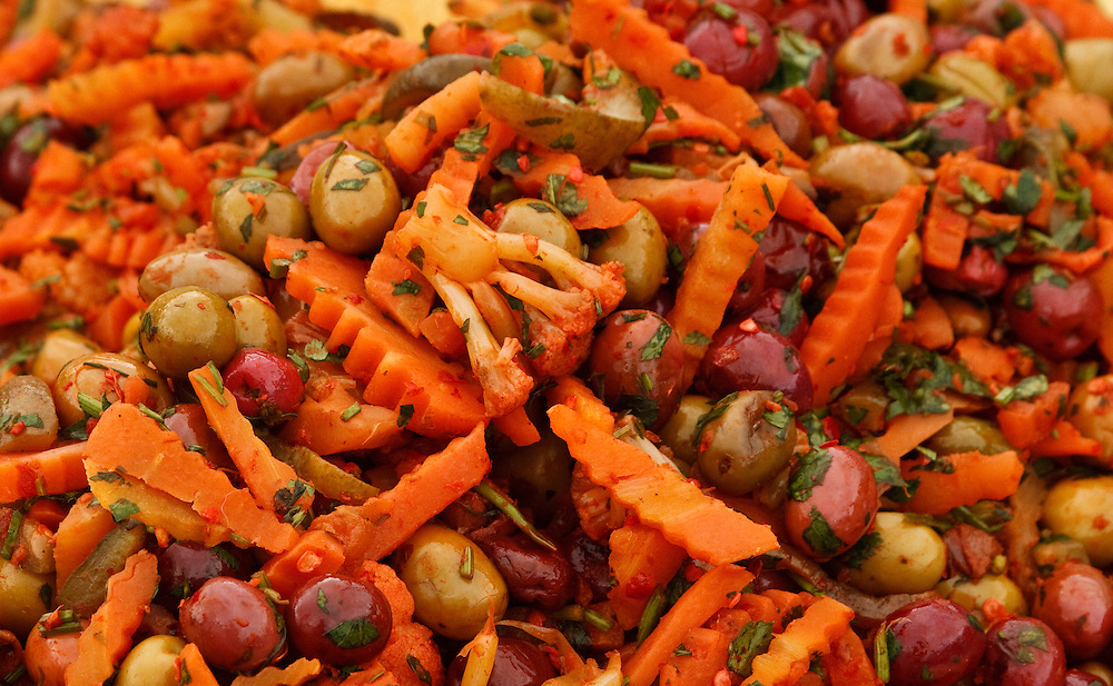 Still life of marinated olives, carrots and herbs at a Moroccan sidewalk vendor.