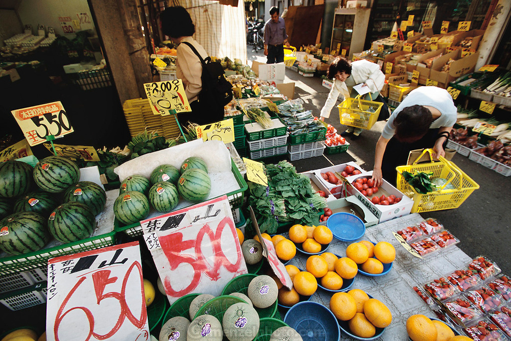 Sayo Ukia (back to camera) shops for fruits and vegetables in the Kodaira City neighborhood, outside Tokyo, Japan, where she and her family live. Because Sayo Ukita buys her family's food from the nearby neighborhood markets situated around the train station (true for many residential areas in Tokyo) she usually shops daily; and by bicycle (the area is congested and there is little parking for cars). From coverage of revisit to Material World Project family in Japan, 2001.