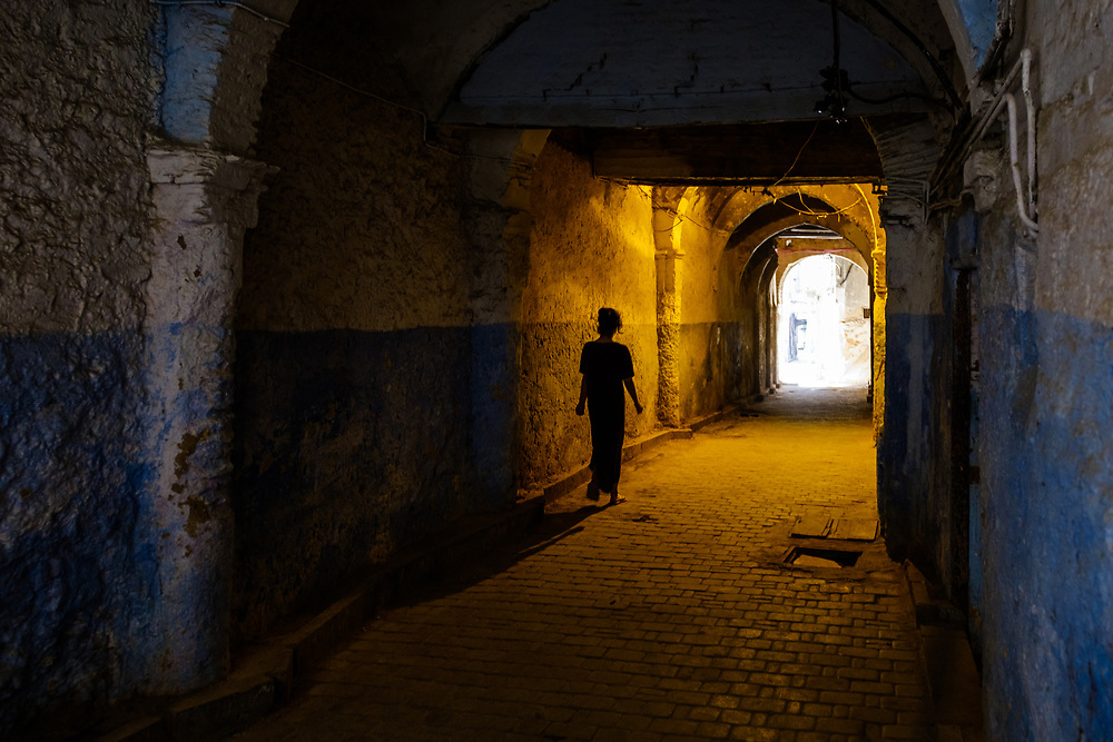 FEZ, MOROCCO - CIRCA APRIL 2017:  Moroccan woman walking on passage at the Medina in Fez