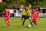Vadaine Oliver tackles Danny Ellis with Callum Nzonca watching on during the Friendly match between Harrogate Town and York City at Wetherby Road, Harrogate, United Kingdom on 25 July 2015. Photo by Simon Davies.