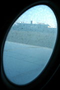Air Koryo flight arrival at Pyongyang, North Korea from Beijing, China. <br />Pyongyang airport terminal seen through a frozen aircraft window<br /><br />Picture Credit: Dermot Tatlow