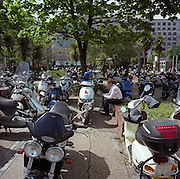 A young city worker reads paperwork surrounded by parked commuter scooters and motorbikes in the City of London.
