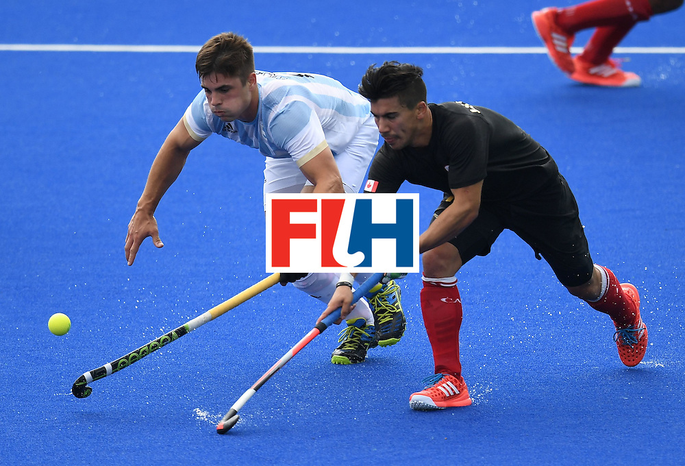 Canada's Gabriel Ho-Garcia (R) and Argentina's Gonzalo Peillat stretche for the ball  during the men's field hockey Canada vs Argentina match of the Rio 2016 Olympics Games at the Olympic Hockey Centre in Rio de Janeiro on August, 8 2016. / AFP / MANAN VATSYAYANA        (Photo credit should read MANAN VATSYAYANA/AFP/Getty Images)