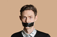 Portrait of a mid adult man with tape on mouth over colored background
