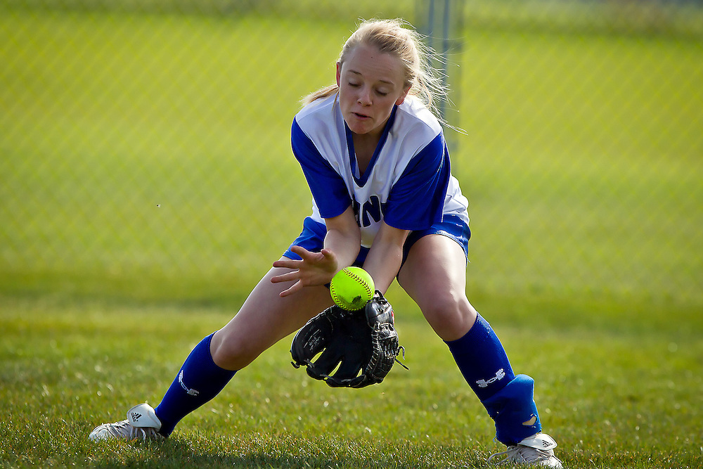 Coeur d'Alene High's Randi Spencer uses her body to keep control of a ball hit to right field during the fourth inning Friday against Lake City High.