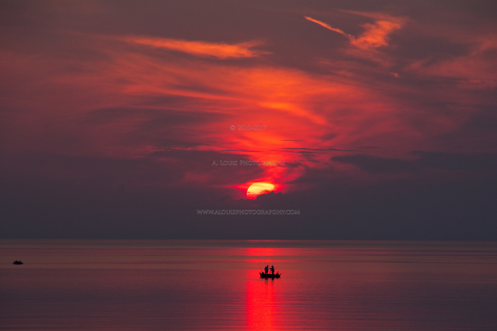 A beautiful scene with a small fishing boat caught in the scarlet red rays of the setting sun on Lake Michigan-- South Haven, MI