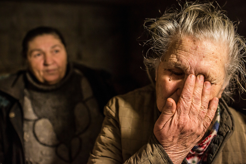DONETSK, UKRAINE - FEBRUARY 3, 2015: Neighbors Vera Dmitrenko, 67, left, and Alla Kozikova, 81 in the basement shelter in which they've been living for days in the Petrovsky district of Donetsk, Ukraine. The neighborhood has been under heavy shelling for the past four days, and a brief pause allowed a few residents to leave their basement hiding places for some fresh air. CREDIT: Brendan Hoffman for The New York Times