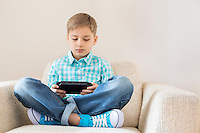 Boy playing hand-held video game on sofa