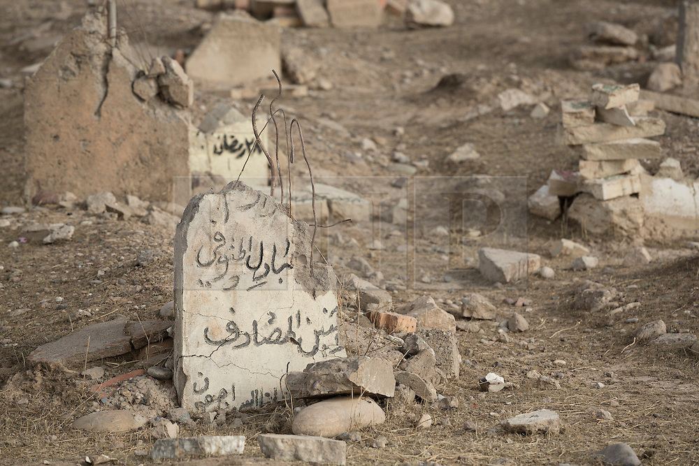 Licensed to London News Pictures. 02/11/2016. Qayyarah, Iraq. Gravestones, smashed by Islamic State militants, litter the Qayyarah Cemetery in the town of Qayyarah, Iraq. The headstones were vandalised by the extremists, who believe that a grave should be flat to the earth and without markings, during the towns two year ISIS occupation.<br /> <br /> Two months after being liberated from the Islamic State, the Iraqi town of Qayyarah, located around 30km south of Mosul, is still dealing with the environmental repercussions of their ISIS occupation. The town's estimated 15,000 inhabitants constantly live under, and in, heavy clouds of smoke which often envelope the settlement. The clouds emanate from burning oil wells in a nearby oil field that were set alight by retreating ISIS extremists after a two year occupation. The proximity of the fires, often right next to homes within the town, covers many buildings and residents with thick soot and will lead to long term health and environmental implications. Photo credit: Matt Cetti-Roberts/LNP