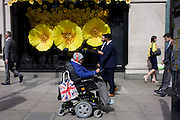 Disabled wheelchair user in front of Apple Watch window display in Selfridges, central London.