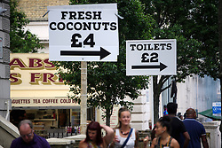 © Licensed to London News Pictures. 29/08/2016. London, UK. Street signs for food and toilets along Ladbroke Grove as Carnival goers enjoy day two of the Notting Hill carnival, the second largest street festival in the world after the Rio Carnival in Brazil, attracting over 1 million people to the streets of West London.  Photo credit: Ben Cawthra/LNP