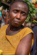 Benin, Abomey-Calavi December 02, 2006 - Woman with tribal scarification on her face. Scarification is used as a form of initiation into adulthood, beauty and a sign of a village, tribe, and clan.