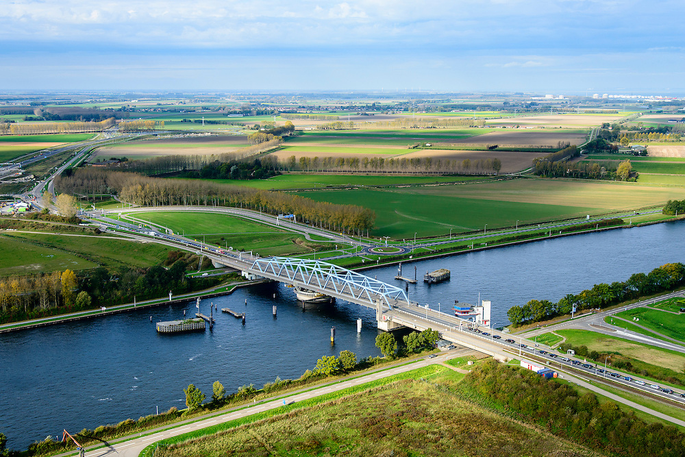Nederland, Zeeland, Zeeuws-Vlaanderen, 19-10-2014; Sluiskil, Kanaal Gent-Terneuzen, kanaalkruising Sluiskil. <br /> De brug in de N61 sluit zeer regelmatig voor zeeschepen en dit veroorzaakt files. Daarom zal de kanaalbrug vervangen worden door een tunnel, de Sluiskiltunnel (oplevering 2015).<br /> The pivot bridge over the canal Gent-Terneuzen (Zeeland) closes very regularly for seagoing vessels and this causes traffic jams. Therefore, the canal bridge will be replaced by a tunnel, the tunnel Sluiskil (completion 2015).<br /> luchtfoto (toeslag op standard tarieven);<br /> aerial photo (additional fee required);<br /> copyright foto/photo Siebe Swart