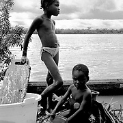 Two young Afro Colombian children wash clothes on the banks of the Rio Atrato in Choco, Colombia. They are some of the countries more than 2 million internally displaced. The jungle area around their village is being fought over by both leftwing rebel groups and rightwing paramilitaries. The inhabitants of many villages have fled to Bellavista. This town was the site of a massacre in May 2002 when a homemade mortar fired by FARC rebels exploded on the roof of a church and killed 119 civillians hiding inside.<br />
