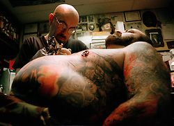 Picture by Mark Larner. Picture shows Lal Hardy tattooing customer Paul at New Wave Tattoo Studio. Paul, a former gardener for the Queen Mother was having a full body-suit of homoerotica finished off in this session...London College of Printing BA (Hon) degree project on tattooing