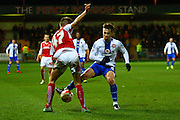 Walsall FC forward Tom Bradshaw challenged by Fleewtood Town Defender Joe Davis during the Sky Bet League 1 match between Fleetwood Town and Walsall at the Highbury Stadium, Fleetwood, England on 15 March 2016. Photo by Pete Burns.