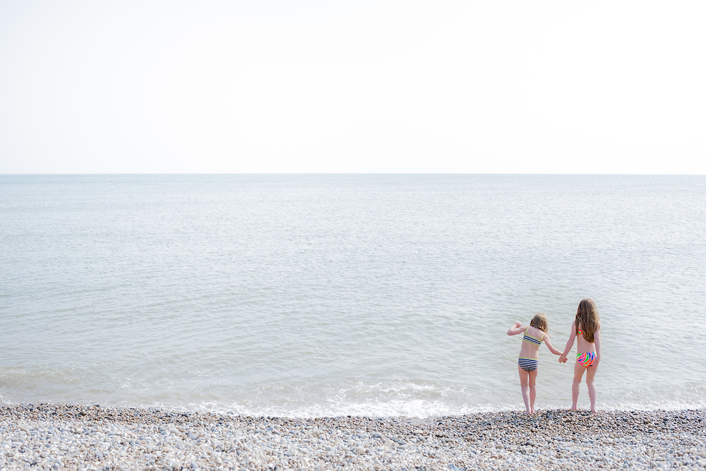 Two young girls thinking about of testing the water temperature on Brighton beach in May 2016