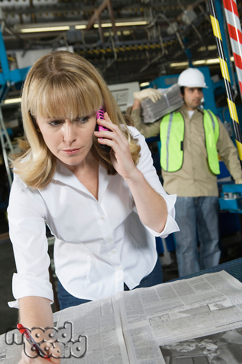 Woman on telephone checking newspapers in factory