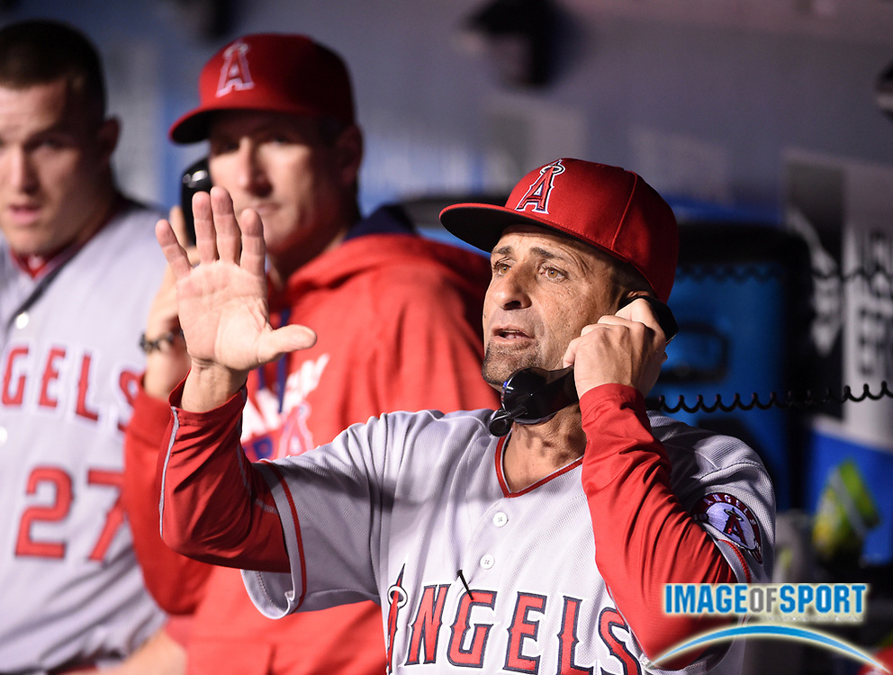 May 16, 2016; Los Angeles, CA, USA; Los Angeles Angels bench coach Dino Ebel (21) talks on the dugout telephone during an interleague MLB game against the Los Angeles Dodgers at Dodger Stadium.