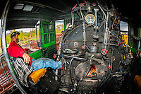 Fireman with steam engine in locomotive, Cumbres & Toltec Scenic Railroad train on the 64 mile run between Antonito, Colorado and Chama, New Mexico.  The railroad is the highest and longest narrow gauge steam railroad in the United States with a track length of 64 miles. The train traverses the border between Colorado and New Mexico, crossing back and forth between the two states 11 times. The narrow gauge track is 3 feet wide.